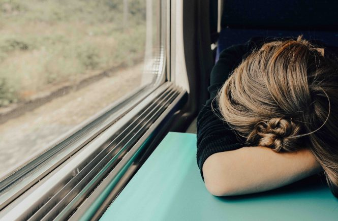 woman with her head down on a train taable, looking stressed